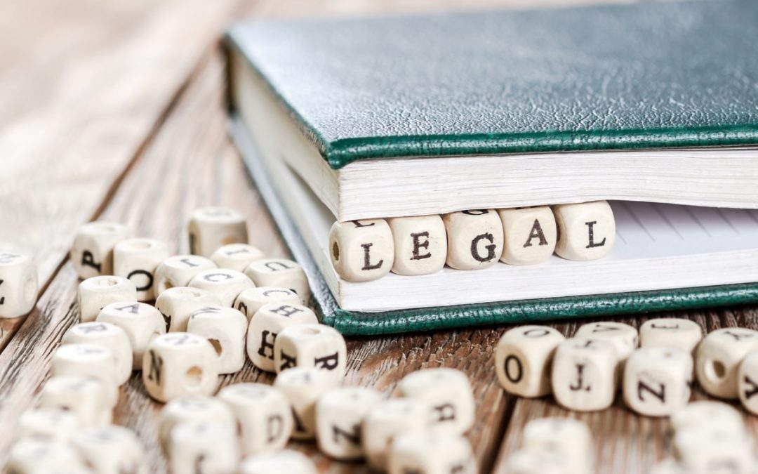 "A blue notebook with scrabble blocks in between the pages. The scrabble blocks spell out to be "" legal."""