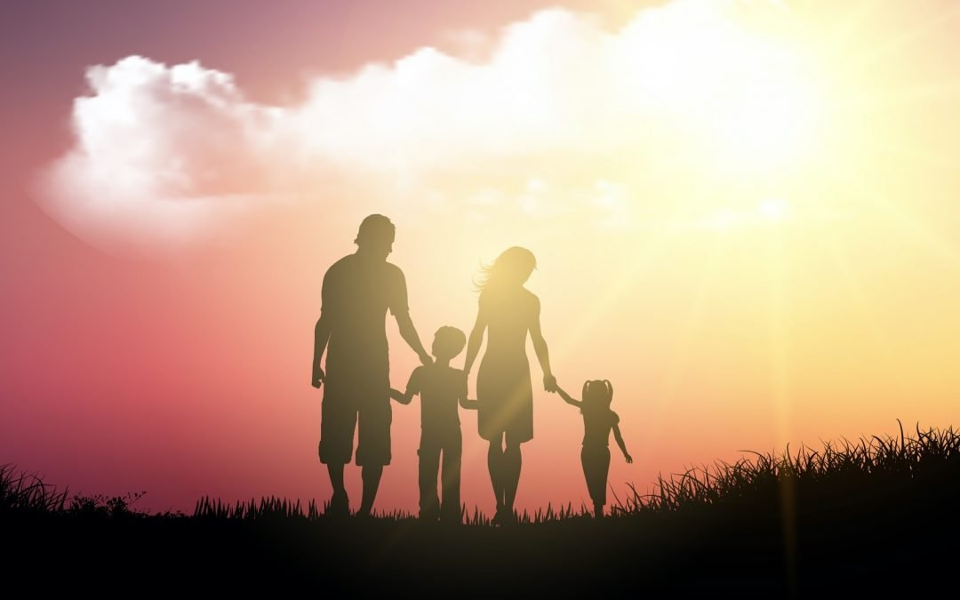A family holding their hands walking on grass under a beautiful sunset