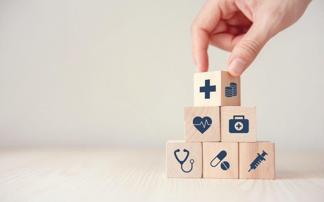 A Hand is flipping a block of wood cubes with health insurance icons on them.