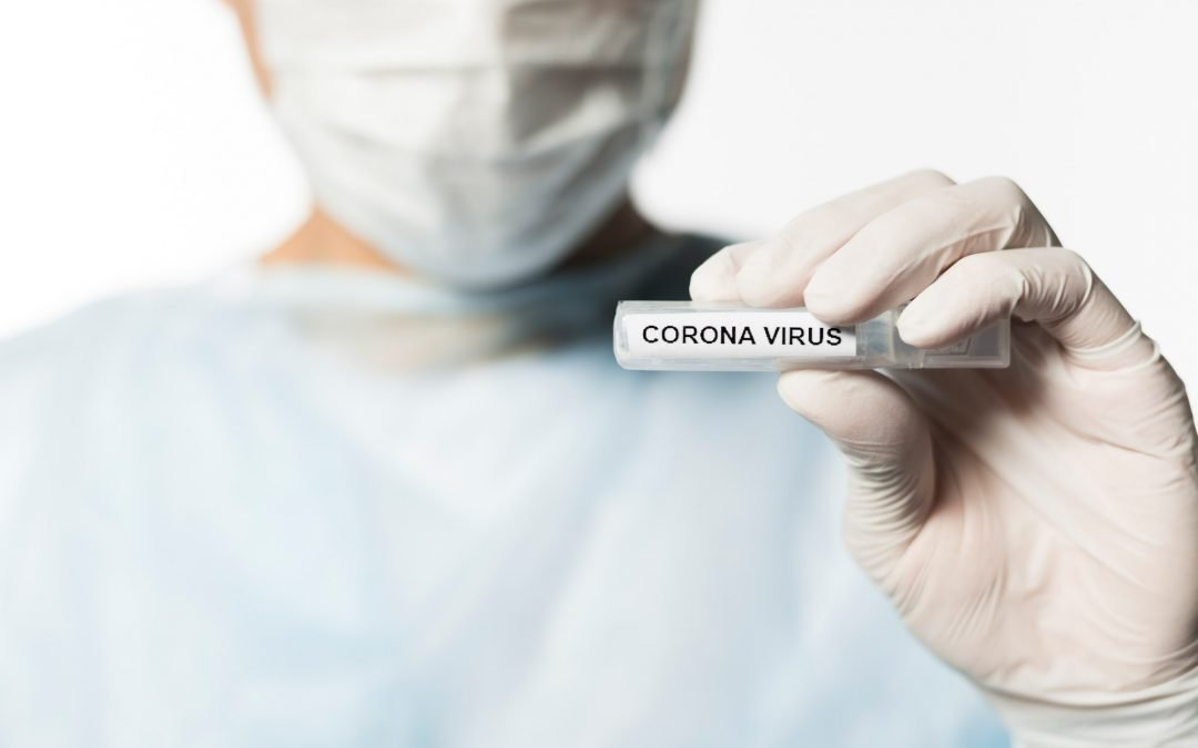 Front view of doctor in PPE holding tube with coronavirus