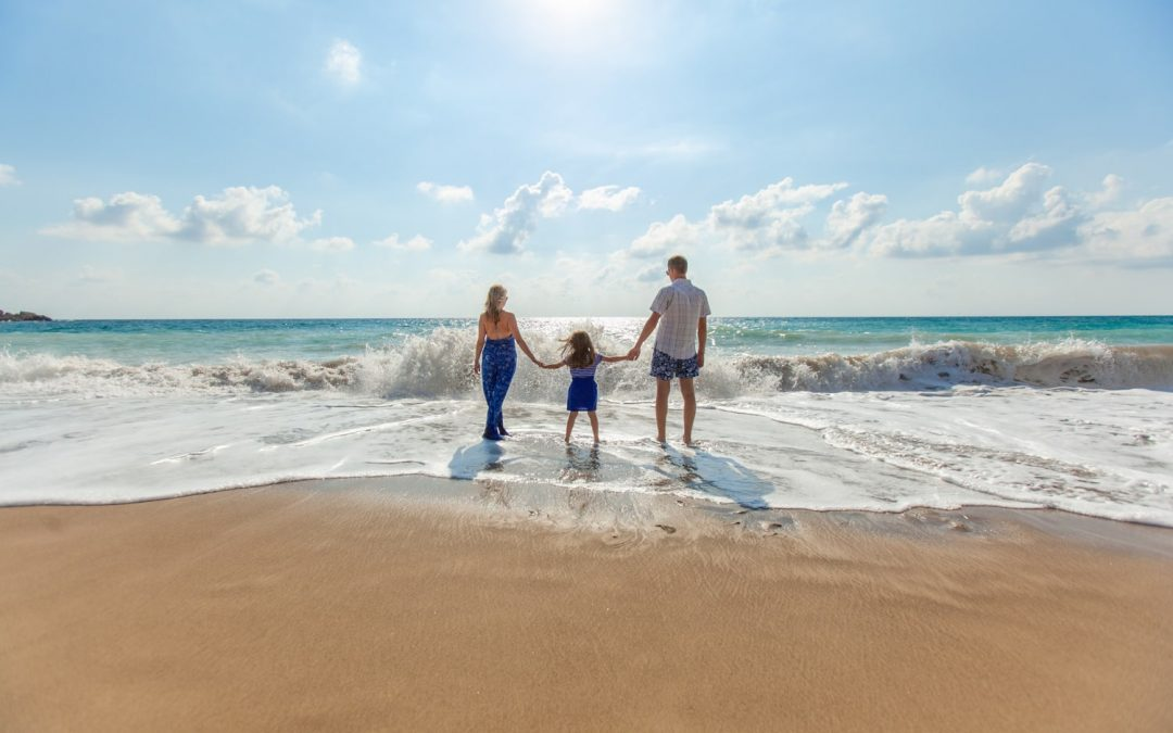 parents holding hands with their child on a beach